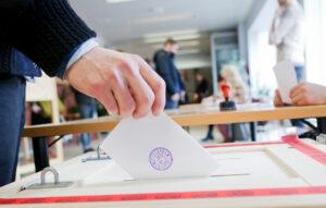 Äänestäjä pudottaa äänestyslipukkeen vaaliuurnaan