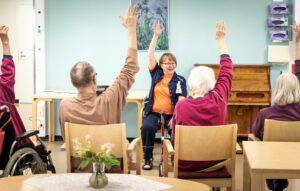 Hoitaja ohjaamassa ikäihmisten tuolijumppaa