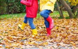 Lapset hyppivät syksyisessä lehtikasassa