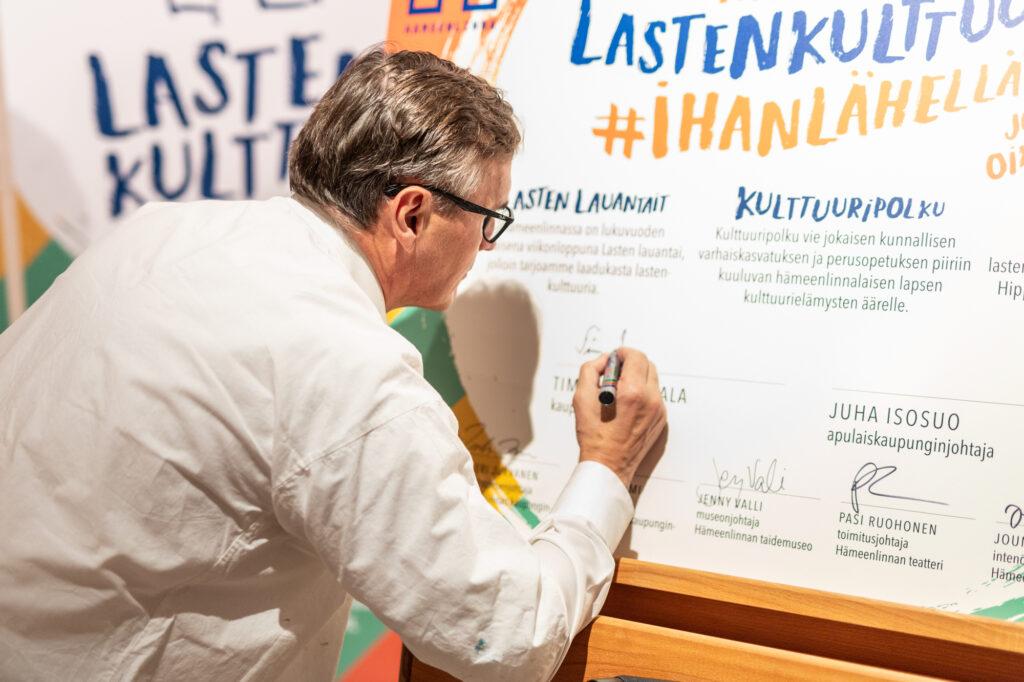 Kj Timo Kenakkala allekirjoittaa lastenkulttuurilupauksen.