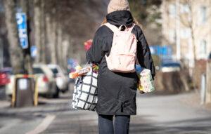 Nainen kävelee kamerasta pois päin kauppakassi kädessään ja reppu selässä.