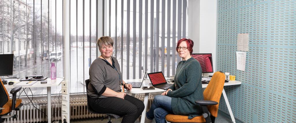 Kaksi naista istuu työpöydän ääressä.