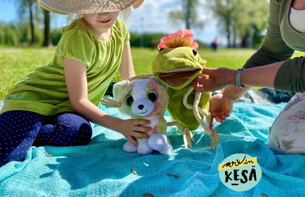 Hattupäinen tyttö viltillä leikkimässä pehmoleluilla. Kuvassa Arxin kesä -logo.