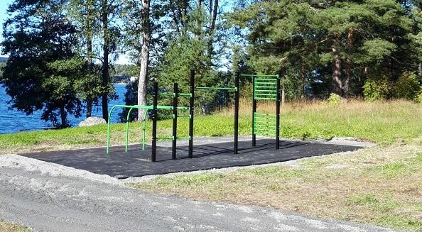 metsän rajaan asennetut vihreän mustat street workout telineet mustalla turva-alustalla