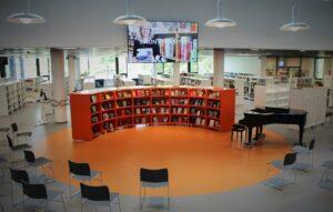 Kirjaston aulassa oleva kirjahyllykkö, jonka ympärillä on tuoleja,