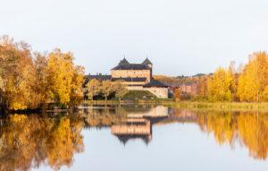 Hämeen linna edustalla järvi sekä syksyisiä puita.