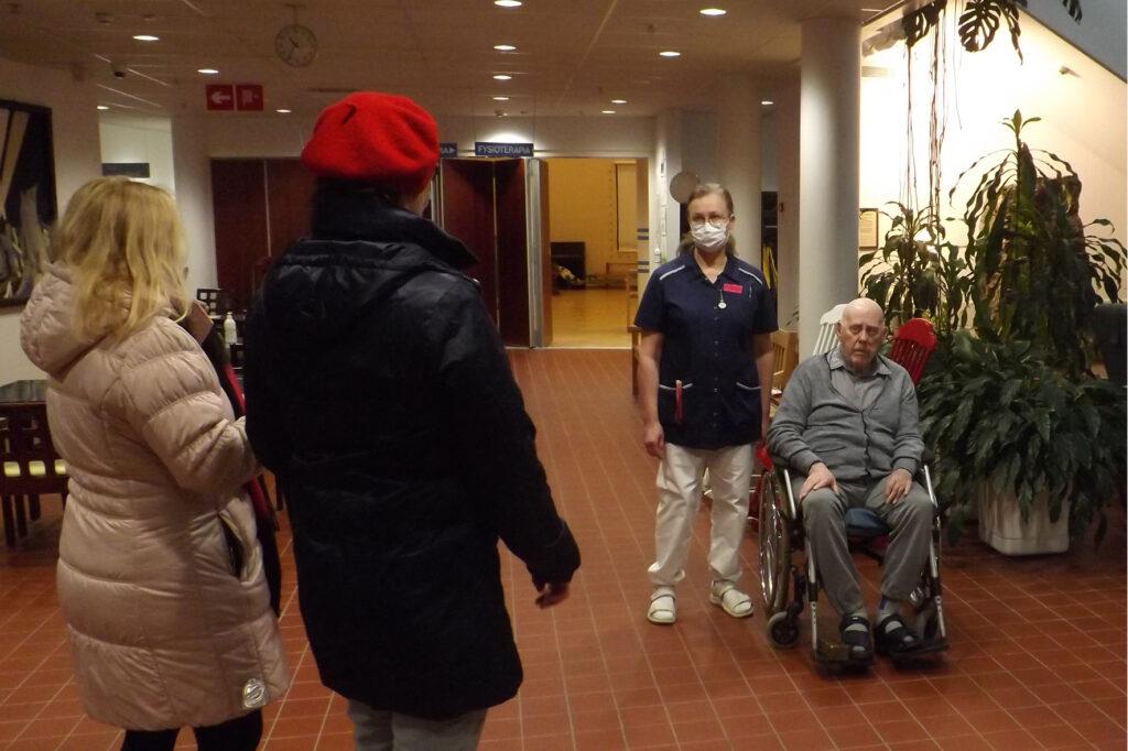 Iäkäs mies istuu pyörätuolissa seuranaan hoitaja ja kaksi vierailijaa.