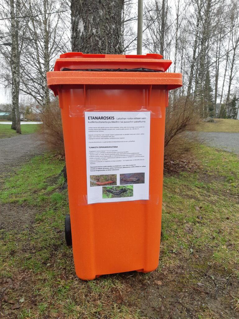 oranssi etanaroskis paikallaan puistossa