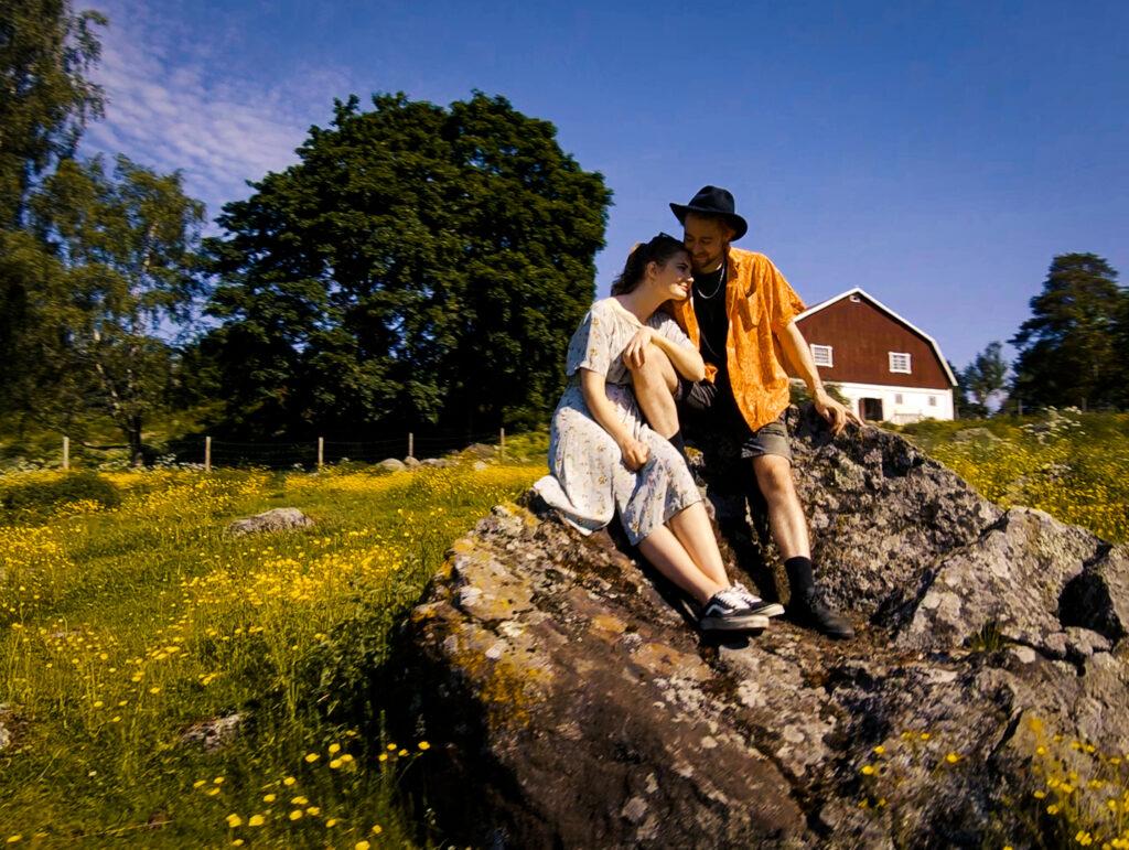 Nuori pariskunta istuu kiven päällä ja halaa