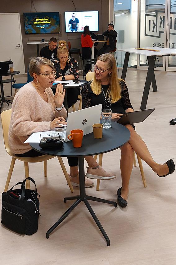 Naiset juttelevat pöydän äärellä