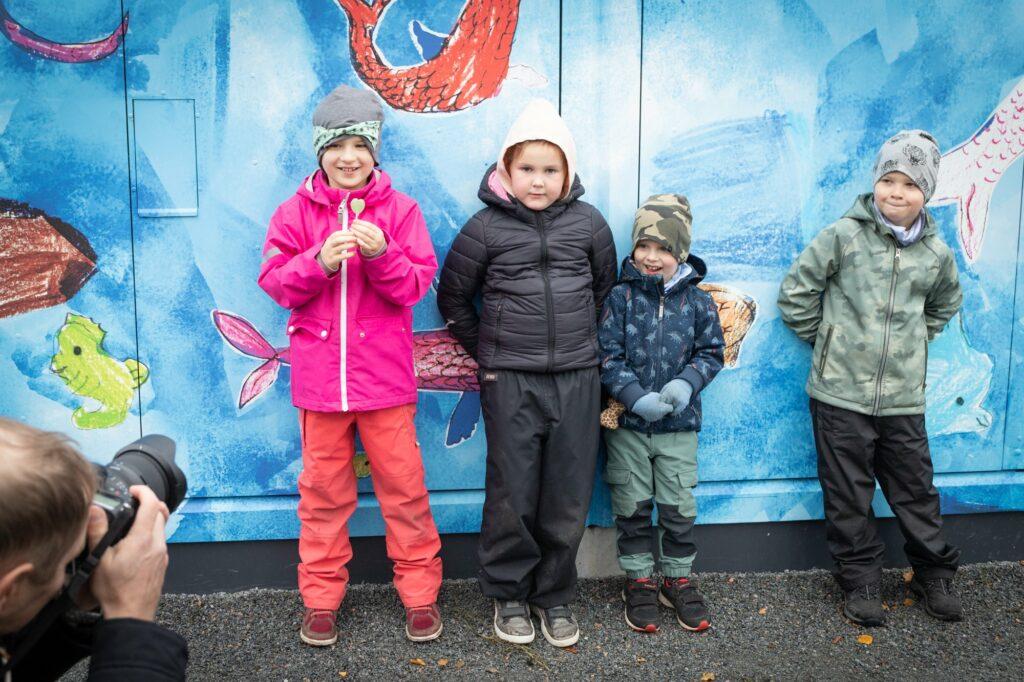 Neljä lasta seisoo värikkään sähkömuuntajan edessä